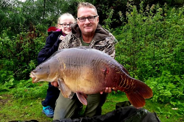 Millie Wailes, seven, and her dad Darrel with the 30lb 4oz mirror carp 'Raspberry' caught at Sandiway Lakes