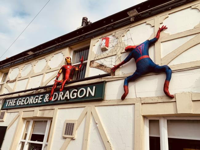 Spiderman and Iron Man scaling the George and Dragon pub during the Glazebury Scarecrow Festival.
