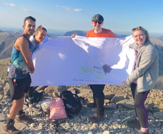 Daniel Gwilliam, Rachel Pepperdine, Andrew Stratford and Melissa Jones holding the Belong flag at the top of the summit