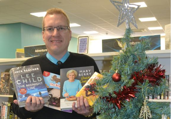 LiveWire community librarian Matthew Entwistle with some of the year's most popular books