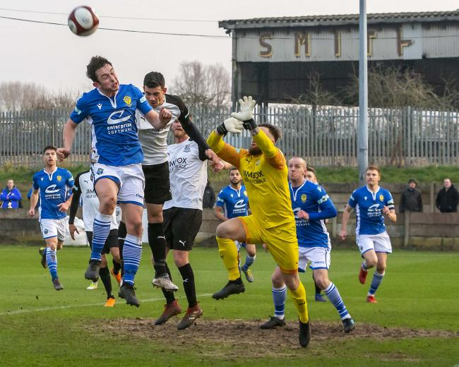 Ben Garrity challenges for a header at Bamber Bridge. Picture by John Hopkins