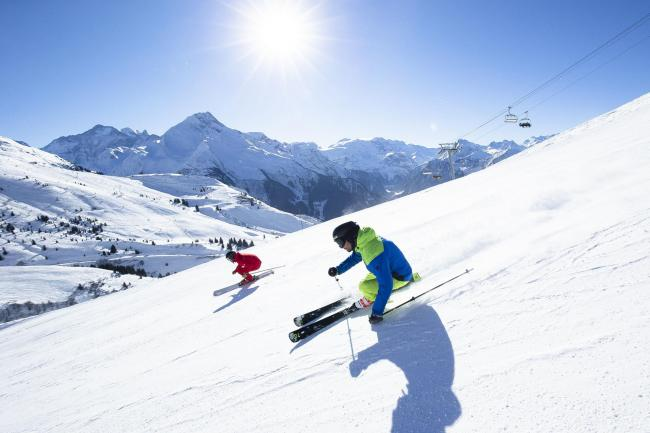 Skiers hurtling down a mountain
