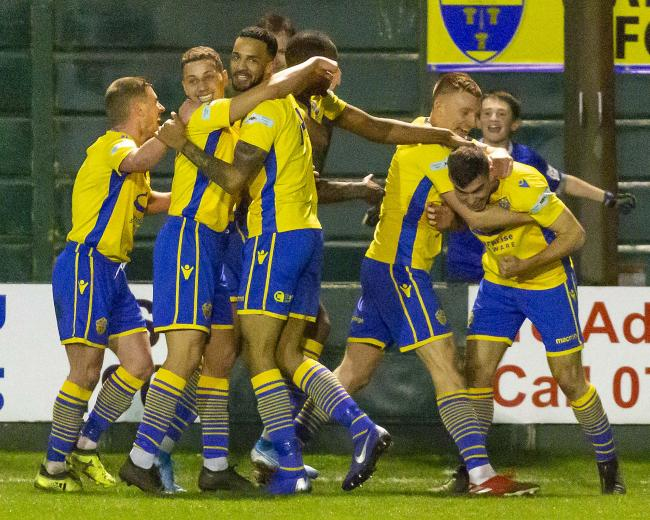 Tom Warren, right, is mobbed after scoring Yellows' dramatic winner against Matlock Town. Picture by John Hopkins