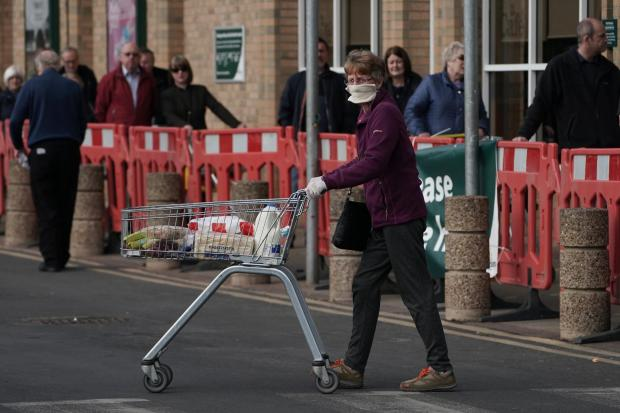 Warrington Guardian: Customers social distancing in a queue outside a Morrisons supermarket