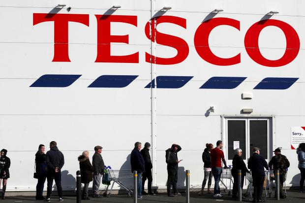 Warrington Guardian: People queue outside a Tesco Extra store in Madeley, Shropshire