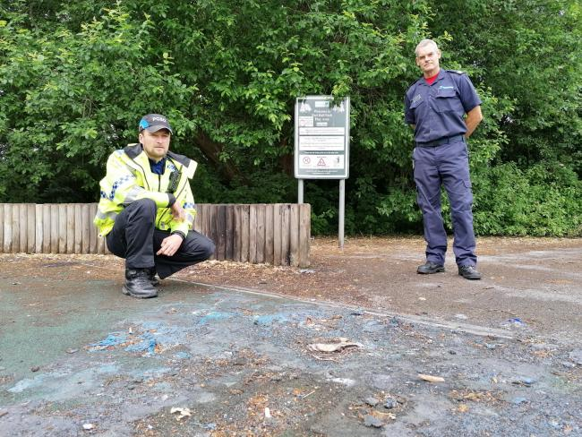 Cheshire Police PCSO Jordan Burke and Cheshire Fire and Rescue Service crew manager Paul Watterson survey damage caused by an arson attack in Peel Hall Park