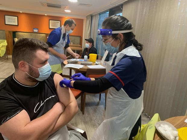 Warrington Guardian: Lewis Smith, support worker at Belong Warrington, is vaccinated by Xiurong Deng, practice nurse at Stockton Heath Medical Centre
