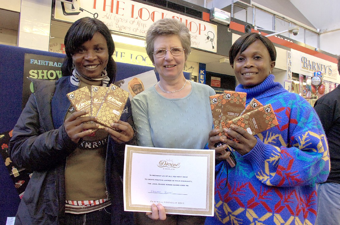 Eleanor Kunar receives a years supply of chocolate with cocoa producers Harriet Boatemaah and Fatima Ali