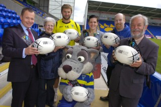 At The Halliwell Jones Stadium with Wolfie are, from left, Labour spokesman for Warrington South Nick Bent, Jackie Hancock, from Fair 4 All, Warrington Market, Wolves prop Paul Wood, fair trade supporters Ali Lancaster and Charlie Browning, and the Rev St