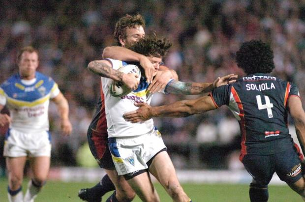 Lee Briers feels the full force of the St Helens defence. Pictures by Mike Boden
