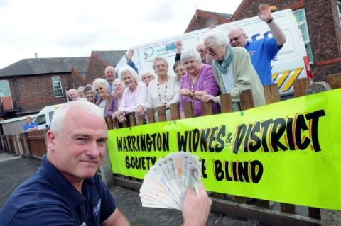 Stuart Chadwick presents the cash to Warrington Blind Society