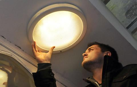 Warrington Guardian: Tom Holmes from St Michael le Belfrey Church changes a light bulb for a neighbour