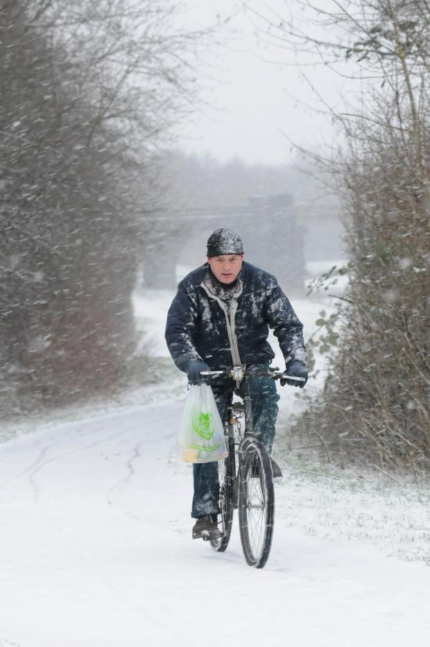 A cyclist braves the worse of the weather at Sankey Valley
