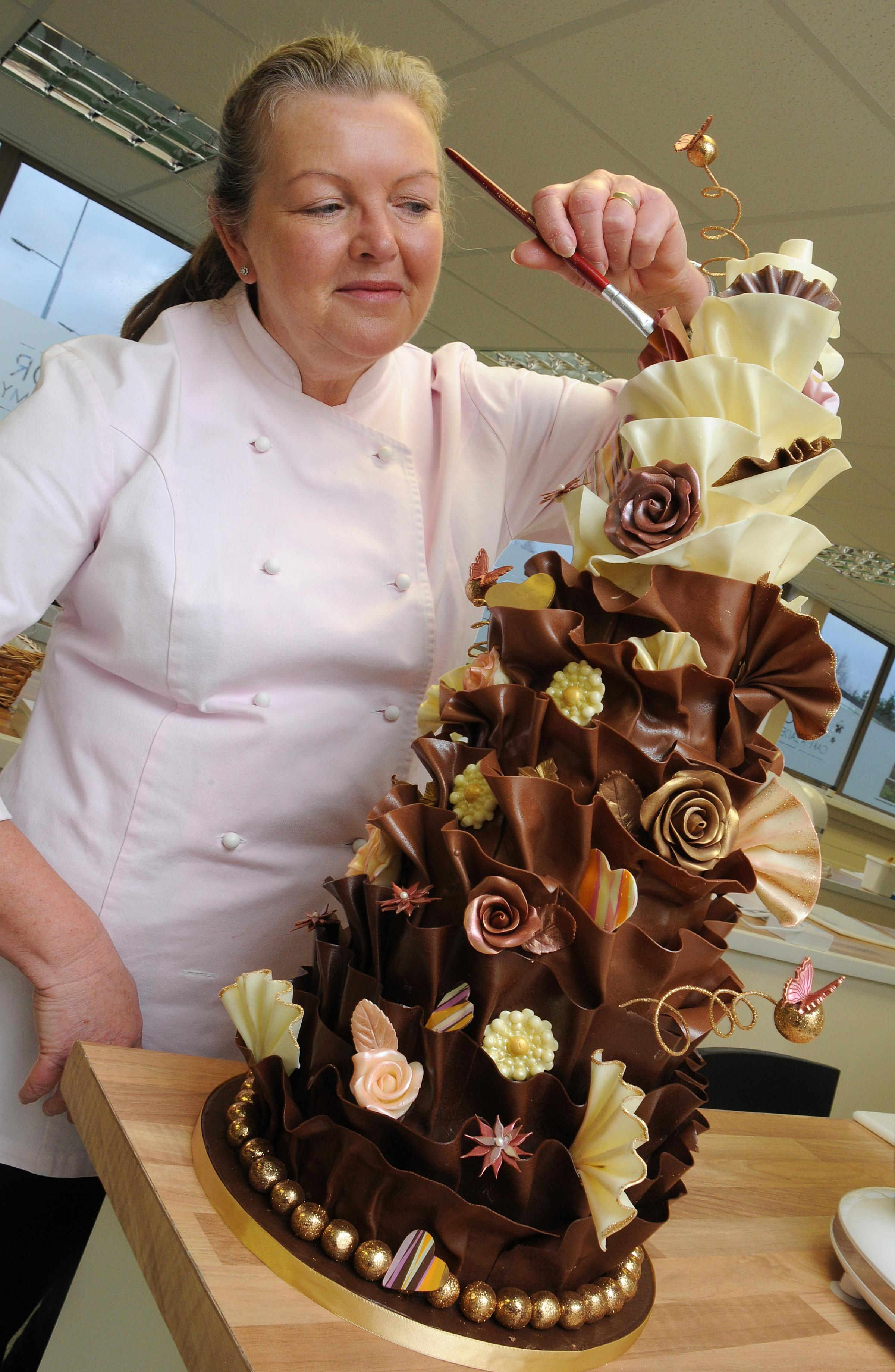Alison Meyrick decorates one of the elaborate cakes in the new Windsor Cake Academy