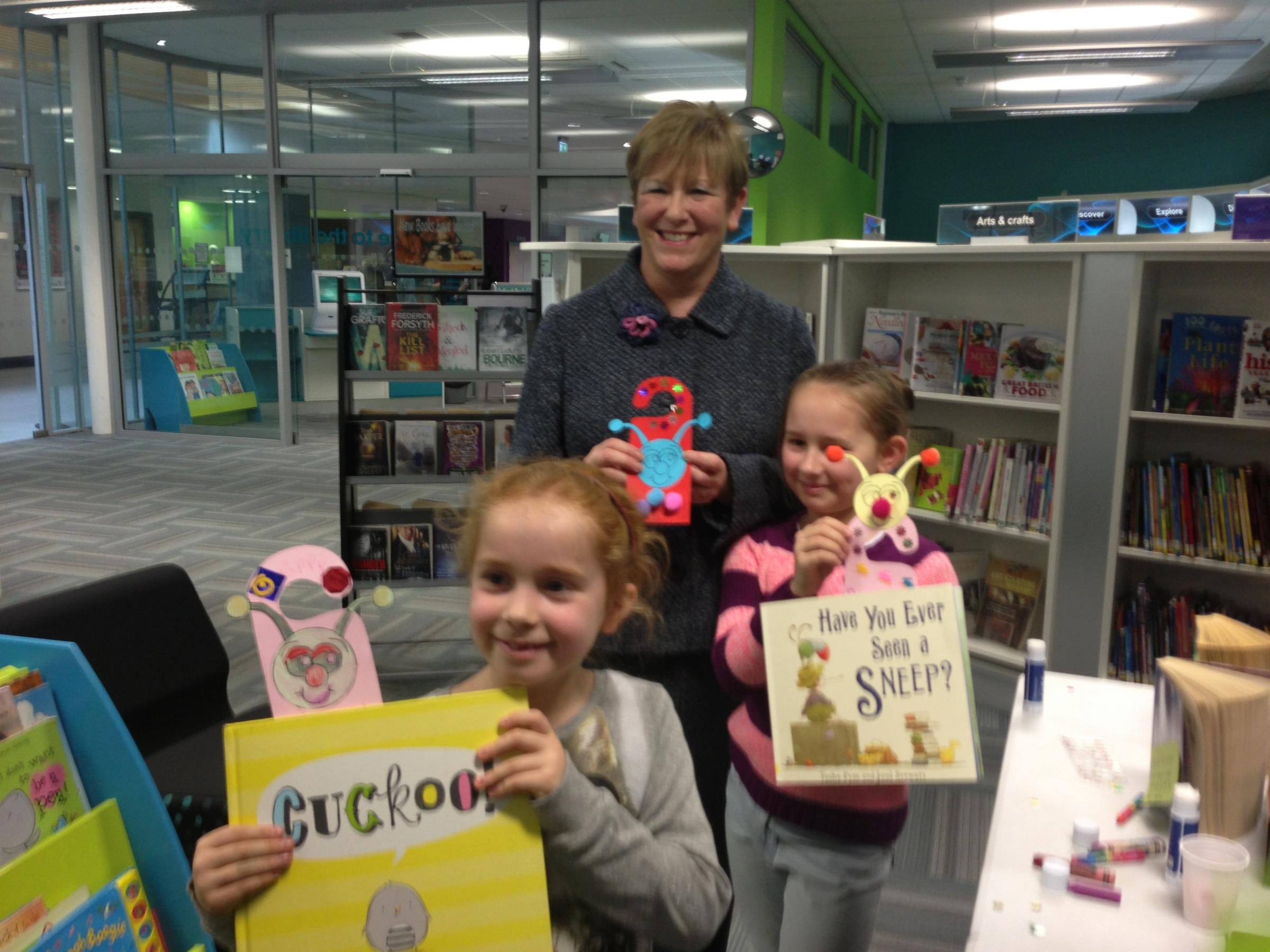 Keira and Poppy Jackson from Winwick with Helen Jones MP at Orford Jubilee Neigbourhood Hub with their bookmarks