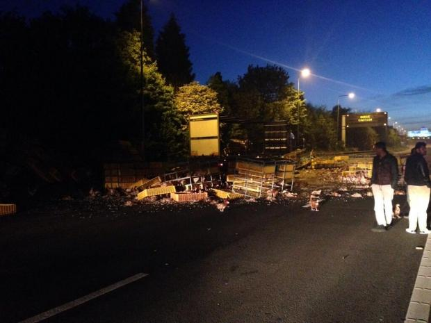 Warrington Guardian: Crash scene: 6,000 live chickens spill across the road. Picture: @IainCPatterson