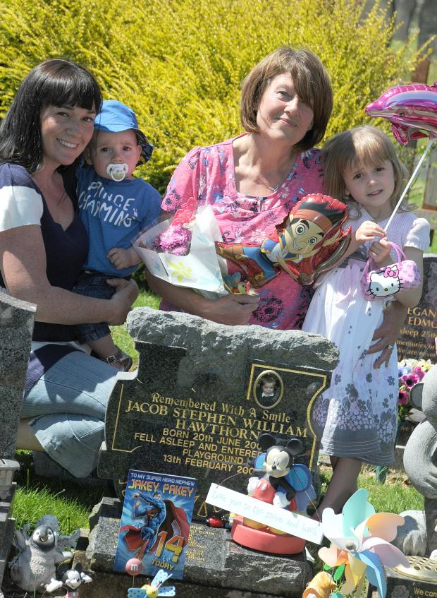 Warrington Guardian: Christine Bentham with Christie Bower, Jacob's mum, and children Darcy, 4, and Rufus, 1, at the grave of jacob on his 14th birthday