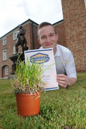 Nicholas Watmough from the Warrington Guardian with the turf which will be planted in The Academy grounds
