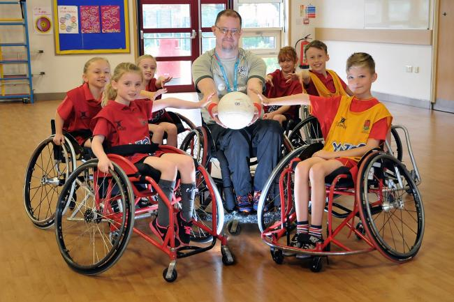 Liverpool Lions Wheelchair Rugby Club player-manager Martin Beddis with Stockton Heath Primary School pupils