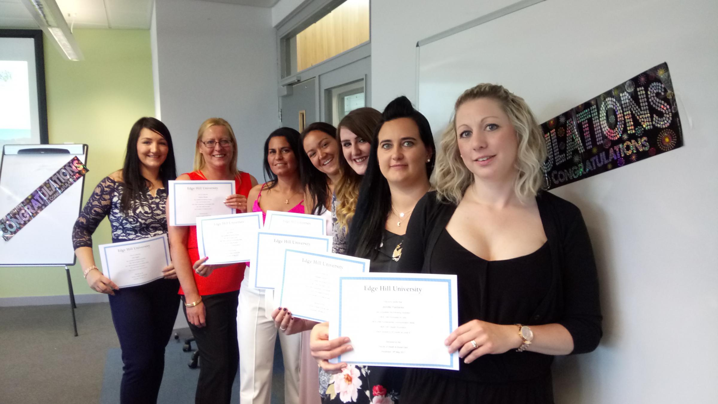 Healthcare assistants celebrate graduating from the programme.