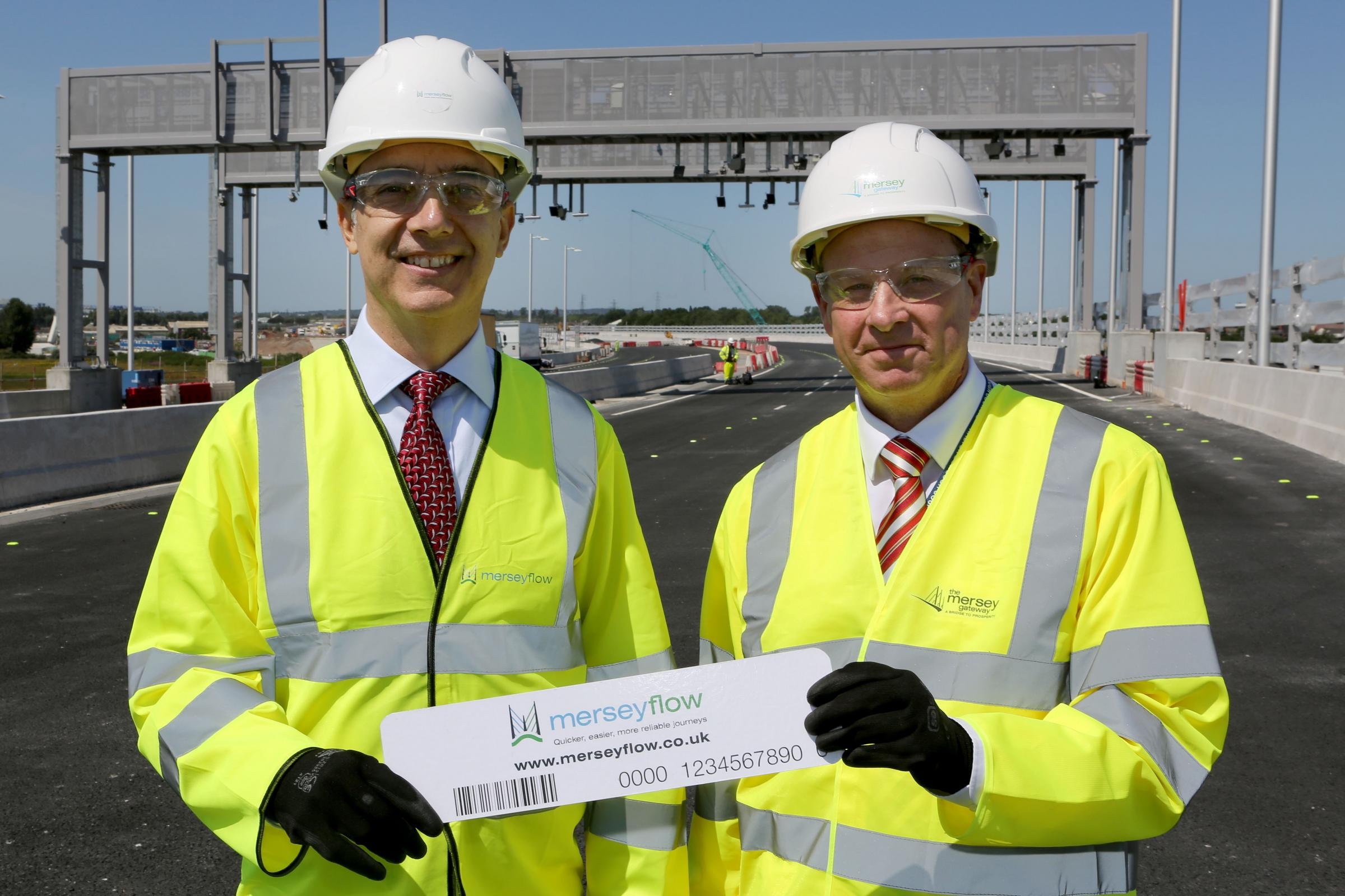 David Parr, chief executive of Halton Borough Council, and Anthony Alicastro, managing director of Merseyflow, in front of the Merseyflow tolling gantry