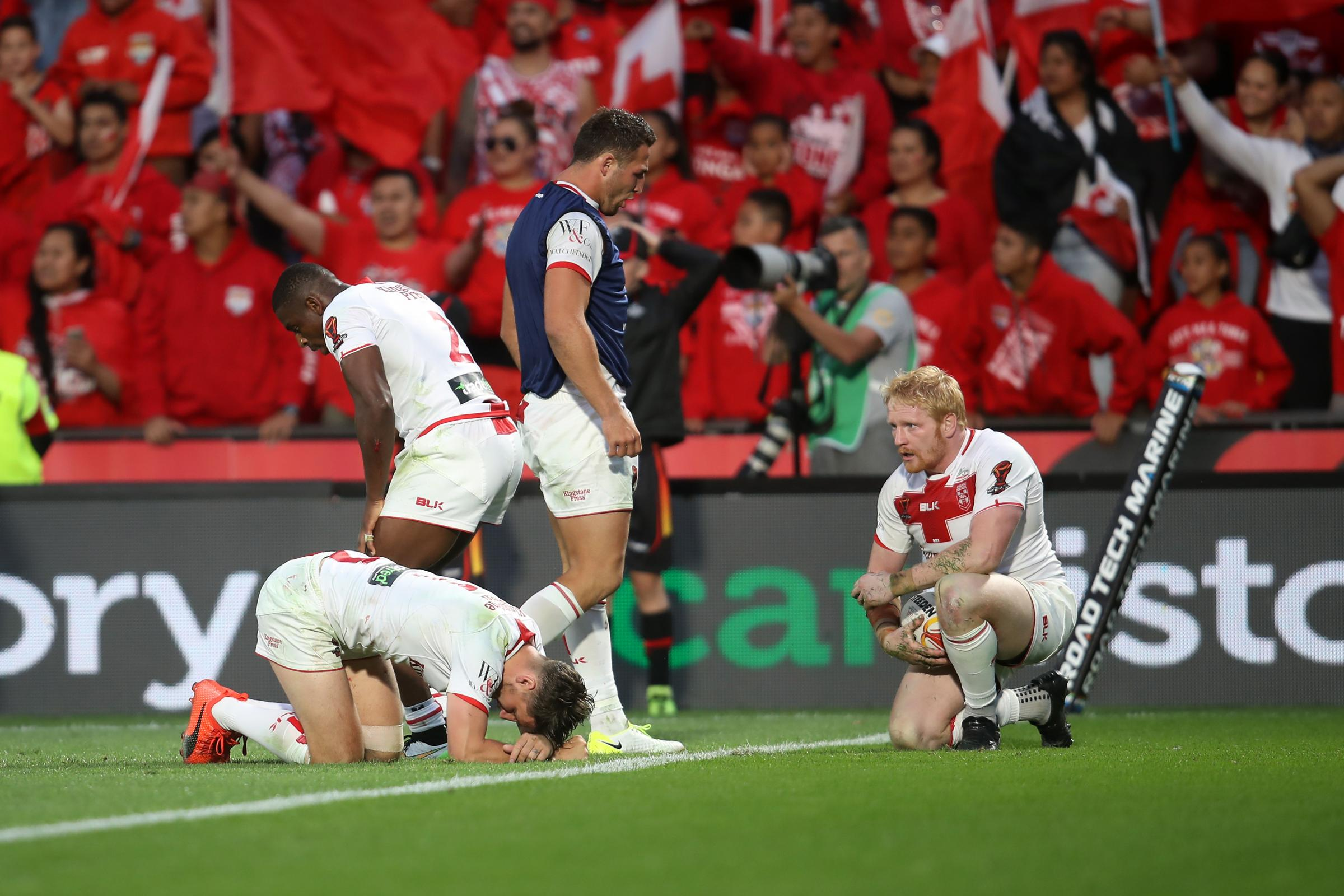 England players lie exhausted on the turf just after Andrew Fifita's try for Tonga is disallowed. Picture by NRLPhotos