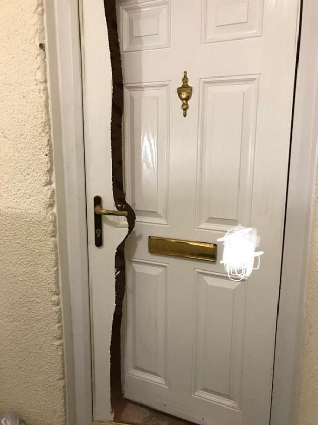 Warrington Guardian: Police have smashed down a door during a raid in Padgate