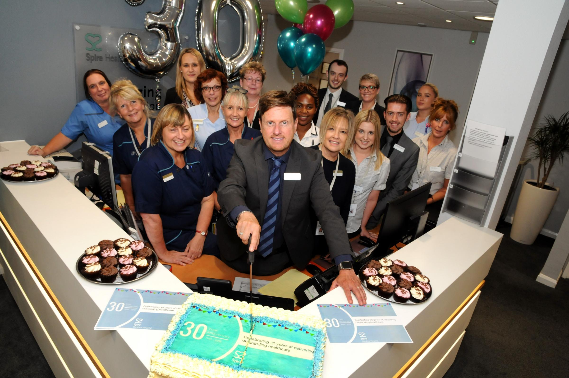 Director Andrew Johnson cuts the cake to celebrate Spire Cheshire Hospital's 30th birthday.