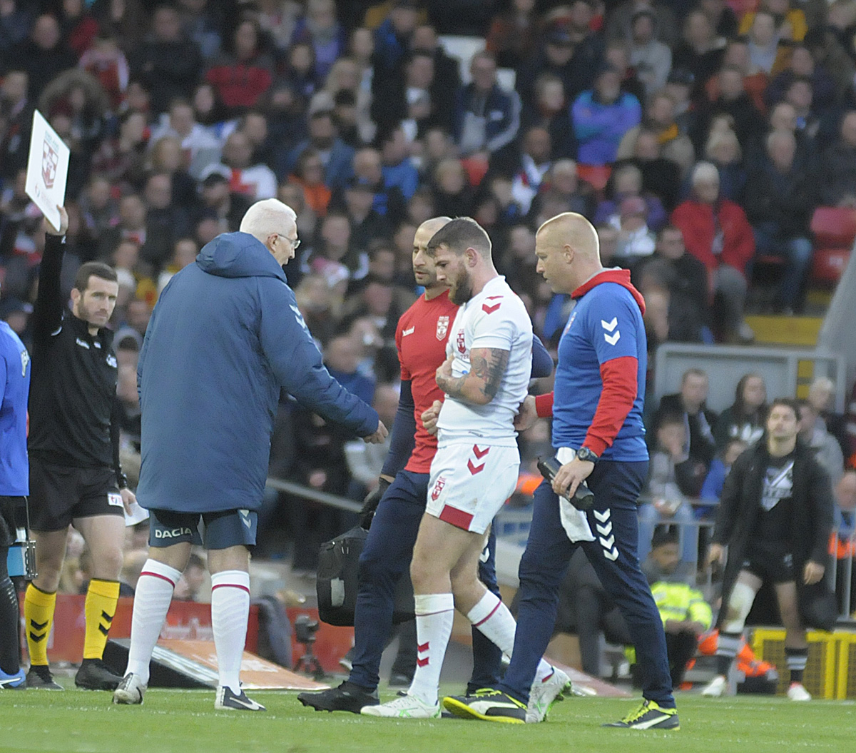 Daryl Clark is helped off by the England medical team. Picture by Mike Boden