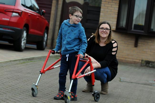 George Jewell-Hanson, pictured with his mum Emma, needs £35,000 for a 'life-changing operation' that will allow him to walk independently for the first time.