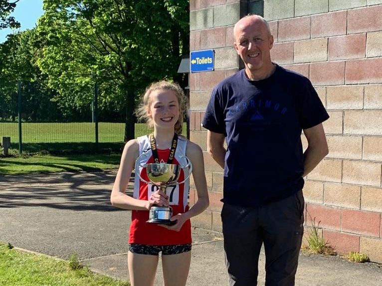 Orla Gregory receives the Marie Birkenhead Trophy from her coach Russell Tart